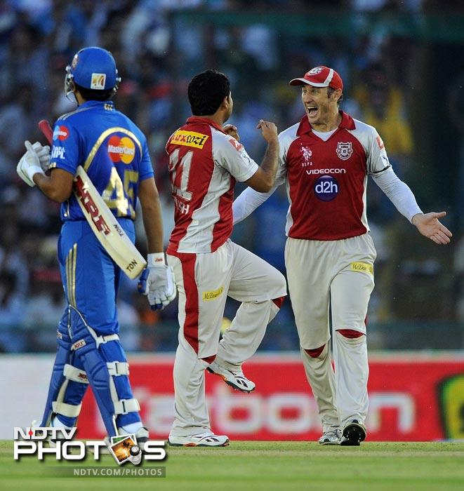 Piyush Chawla celebrates the wickets of Dinesh Karthik with David Hussey during the IPL Twenty20 match between Kings XI Punjab and Mumbai Indians at PCA Stadium in Mohali. (AFP Photo)