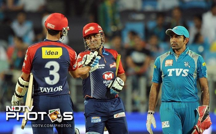 Delhi Daredevils captain Virender Sehwag celebrates victory with teammate Ross Taylor as Pune Warriors India wicketkeeper Robin Uthappa watches after the IPL Twenty20 match at the Sahara Stadium in Pune. (AFP Photo)