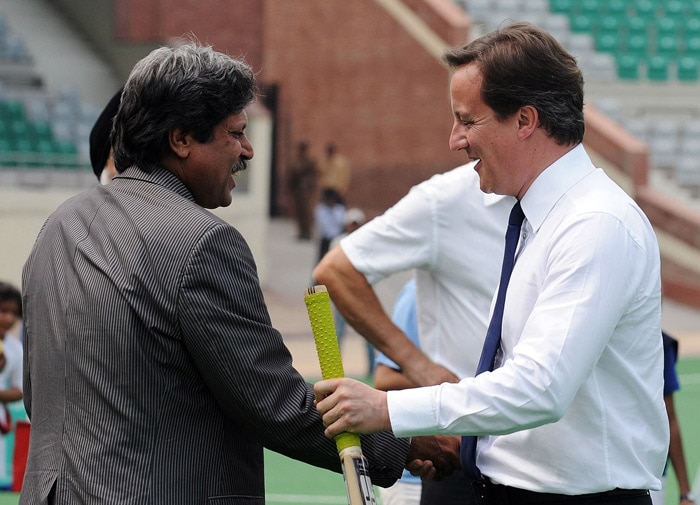 British Prime Minister David Cameron shakes hands with former Indian cricket captain Kapil Dev after playing cricket during a visit to the National Stadium in New Delhi. (AFP Photo)