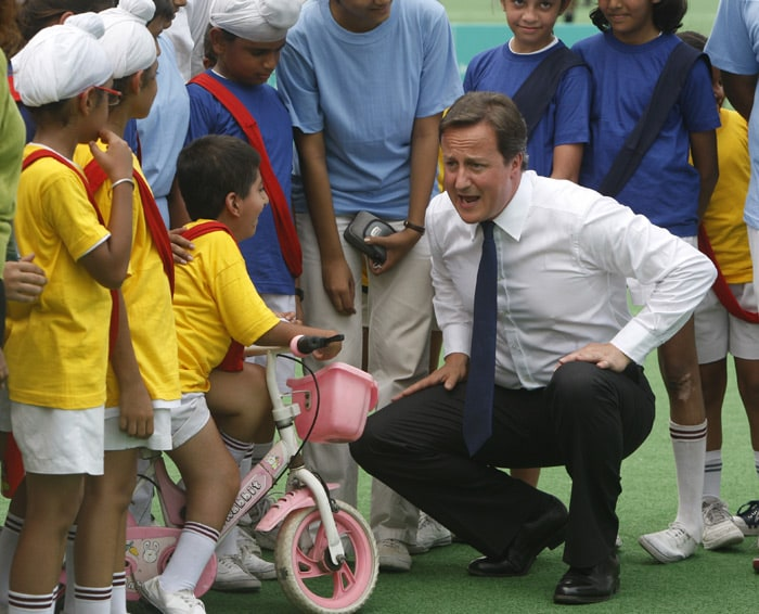 British Prime Minister David Cameron (right) interacts with children at the national hockey stadium in New Delhi. (AP Photo)