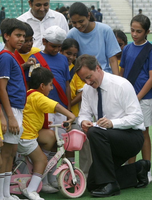 British Prime Minister David Cameron (center) signs autograph during an interaction with children at the national hockey stadium in New Delhi. (AP Photo)