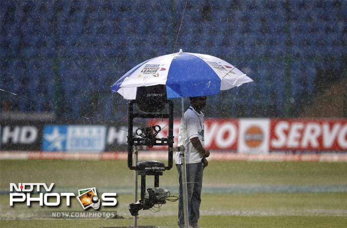 A cameraman stands under an umbrella as rains lashed Bangalore. The match had to be delayed by half an hour.