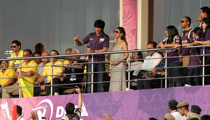 Kolkata Knight Riders team owner Shah Rukh Khan, center left, acknowledges the crowd as his wife Gauri stands beside him during the Indian Premier League cricket match against Chennai Super Kings at the Eden Garden Stadium. (AP Photo)