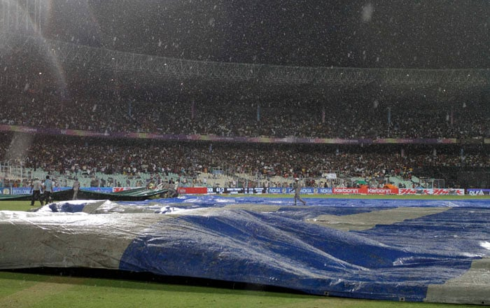Groundsmen cover the field as rain stops the Indian Premier league match between Kolkata Knight Riders and Chennai Super Kings at the Eden Garden Stadium. Kolkata won by 10 runs on D/L method. (AP PHOTO)