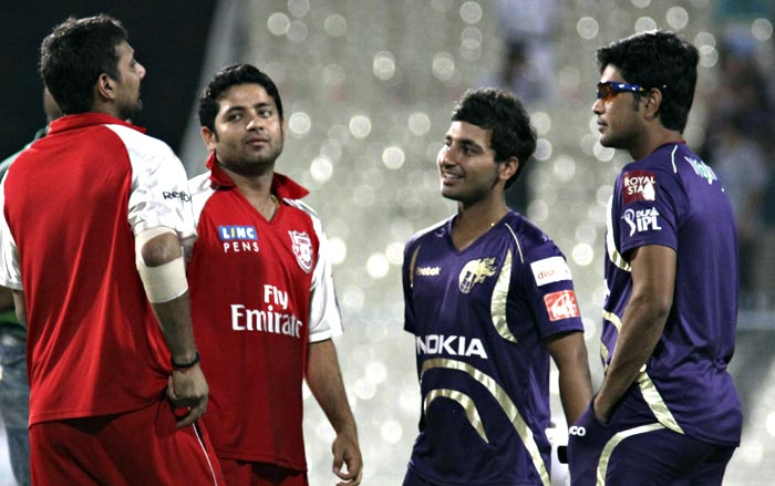 Kings XI Punjab cricketers Praveen Kumar (L) and Piyush Chawla (2nd L) interact with Kolkata Knight Riders players Shreevats Goswami (2nd R) and Laxmi Ratan Shukla (R) before the IPL Twenty20 cricket match between the two teams at the Eden Gardens Stadium. (AFP PHOTO)