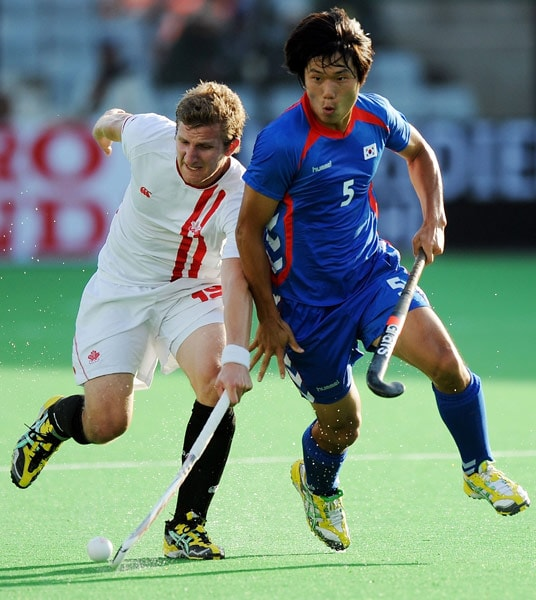 South Korean hockey player Nam Hyun Woo (R) vies for the ball with Canadian hockey player Mark Pearso (L) during their World Cup 2010 match at the Major Dhyan Chand Stadium in New Delhi. (AFP Photo)