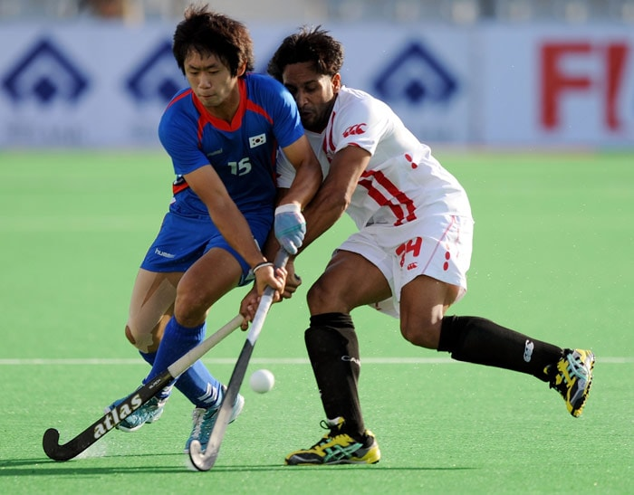 South Korean hockey player Kang Moon Kyu (L) vies for the ball with Canadian hockey player Gabbar Singh (R) during their World Cup 2010 match at the Major Dhyan Chand Stadium in New Delhi. (AFP Photo)