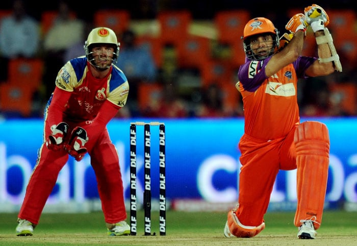 Kochi Tuskers Kerala batsman V.V.S. Laxman (R) is watched by Royal Challengers Bangalore wicketkeeper AB de Villiers as he plays a shot during the IPL Twenty20 match against Royal Challengers Bangalore at the Jawaharlal Nehru International Stadium in Kochi. (AFP PHOTO)
