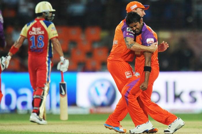 Kochi Tuskers Kerala fielder Brendon McCullum congratulate bowler Vinay Kumar (R) for taking the wicket of Royal Challengers Bangalore batsman Virat Kohli (L) during the IPL Twenty20 match at the Jawaharlal Nehru International Stadium in Kochi. (AFP PHOTO)