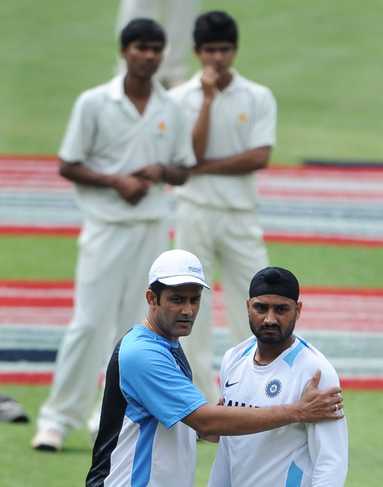 Former Indian cricket captain Anil Kumble gives bowling tips to Harbhajan Singh (R) as young local players look on in the background during a training session for the Indian cricket team at Chinnaswamy Stadium in Bangalore. (AFP PHOTO)