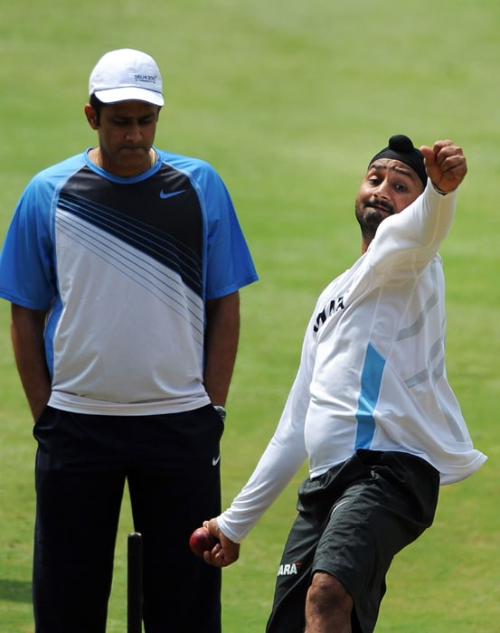 Indian cricketer Harbhajan Singh (R) bowls at the nets as former Indian captain Anil Kumble looks on during a training session for the Indian cricket team at Chinnaswamy Stadium in Bangalore. (AFP PHOTO)