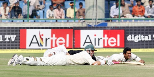 Matthew Hayden and Anil Kumble lie down on ground to avoid bees during the third Test between Indian and Australia in New Delhi.