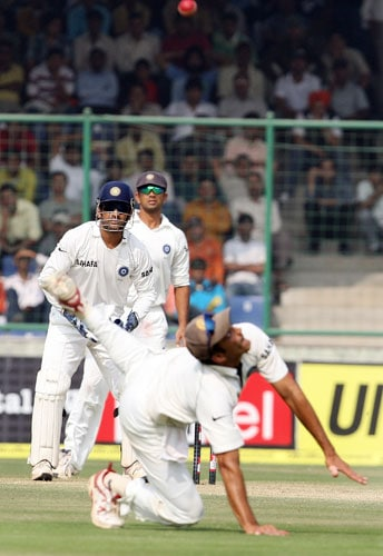 Mahendra Singh Dhoni and Rahul Dravid look on as Anil Kumble unsuccessfully dives in an attempt to take the catch of Matthew Hayden during the third Test match between India and Australia in New Delhi.