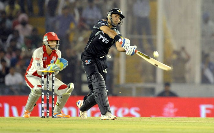 Pune Warriors captain Yuvraj Singh plays a shot as Kings XI Punjab wicketkeepter and captain Adam Gilchrist (L) looks on during the IPL Twenty20 cricket match at the Punjab Cricket Association Stadium in Mohali. (AFP Photo)
