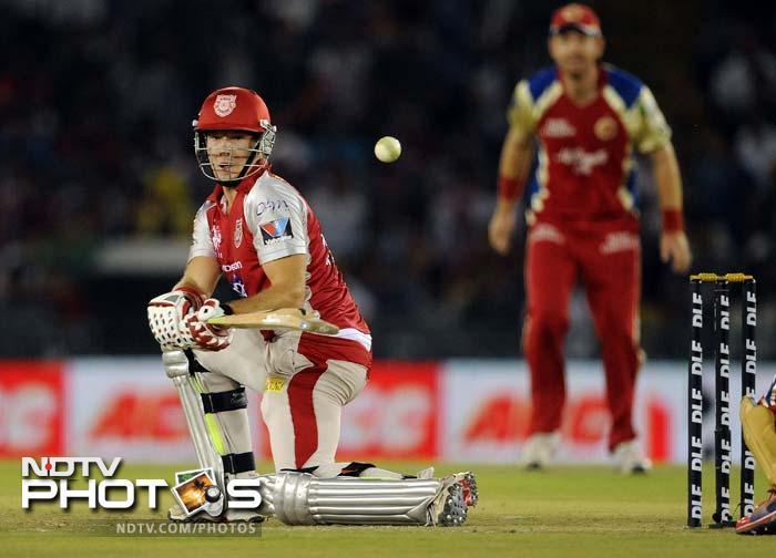 Kings XI Punjab batsman David Miller (L) plays a shot during the IPL Twenty20 cricket match against Royal Challengers Bangalore at PCA Stadium in Mohali. (AFP PHOTO/Prakash SINGH)