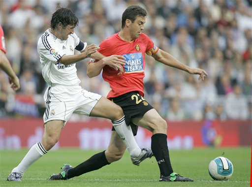 Real Madrid player Raul Gonzalez, left, duels for the ball with Mallorca player Sergio Ballesteros, right, during their Spanish League soccer match against Mallorca in Madrid.