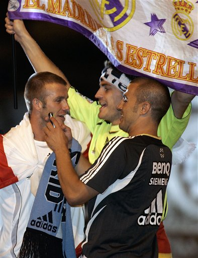 Real Madrid players David Beckham from England, left, Iker Casillas from Spain, center and Fabio Cannavaro from Italy, right, celebrate on their bus at Cibeles square after winning Spanish soccer league title in Madrid.