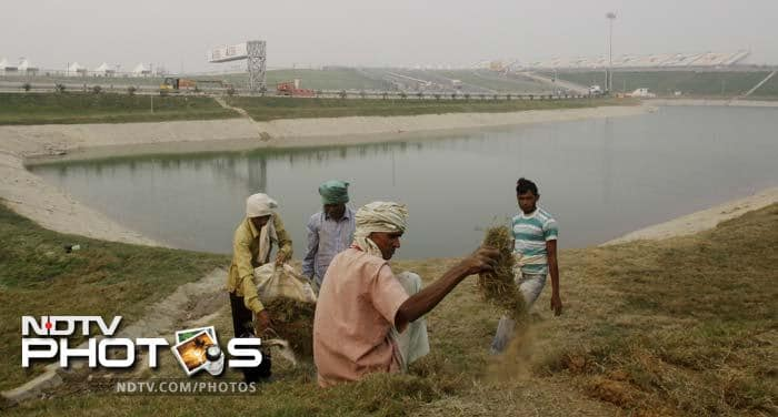 Farmers take a break outside the periphery as the main grandstand of the circuit can be seen in the background.