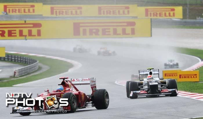 Ferrari driver Fernando Alonso of Spain takes the lead followed by Sauber-Ferrari driver Sergio Perez of Mexico (R) during Formula One's Malaysian Grand Prix at the Sepang International Circuit.