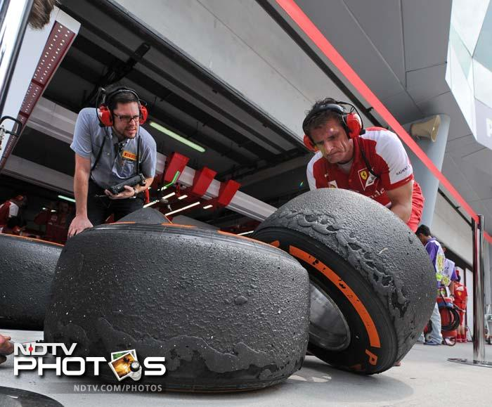 Ferrari crew members look at the wear and tear on tyres during the first practice session at Sepang on March 22, 2013.