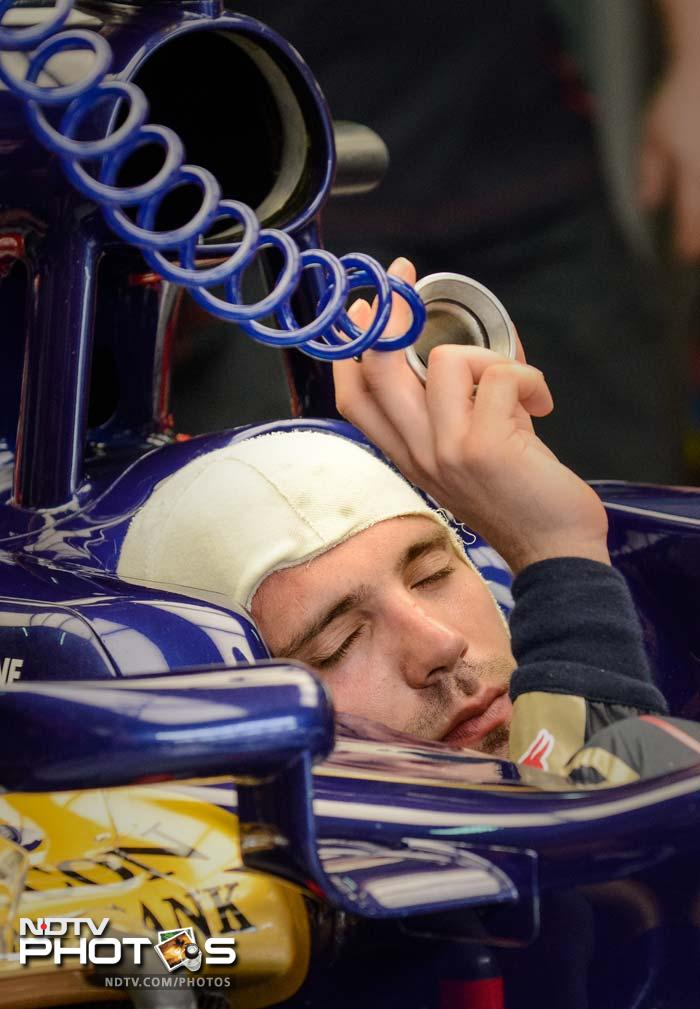 Toro Rosso driver Jean-Eric Vergne of France uses an electric fan to keep himself cool as he sits in his car in the garage during the second practice session of the Malaysian Grand Prix in Sepang.