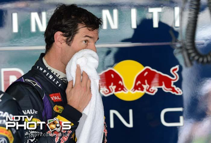 Red Bull driver Mark Webber of Australia wipes his face in the garage after finishing on top in the first practice session of the Malaysian Grand Prix.