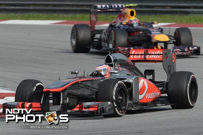McLaren driver Jenson Button of Britain chased by Red Bull driver Mark Webber of Australia during the second Grand Prix of the season at Sepang circuit