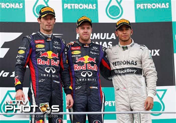 Red Bull driver Sebastian Vettel of Germany, his team-mate Mark Webber of Australia, and Mercedes driver Lewis Hamilton of Britain pose together after awards ceremony at Sepang, Malaysia.