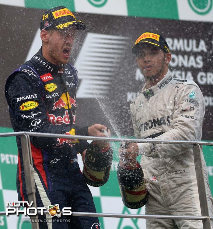Red Bull driver Sebastian Vettel is sprayed with champagne after his victory by third-placed Mercedes driver Lewis Hamilton on the podium after winning the race.