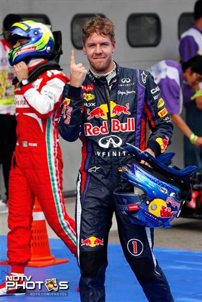 Red Bull driver Sebastian Vettel of Germany celebrates after taking the pole position for Sunday's Malaysian Grand Prix at Sepang.