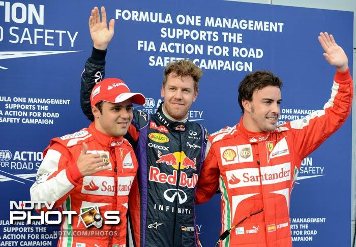 Germany's Sebastian Vettel (centre) after qualifying in the pole position ahead of Ferrari drivers Felipe Massa of Brazil (left) and Fernando Alonso of Spain (R).