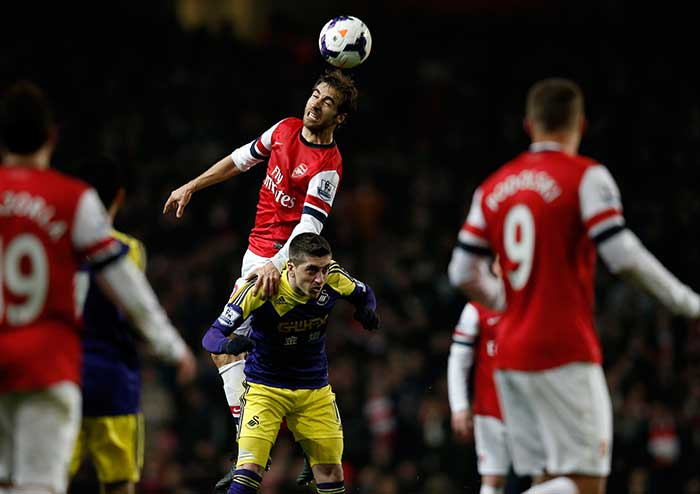 Arsenal's spluttering title challenge suffered another major blow as Mathieu Flamini's last-gasp own goal forced the Gunners to settle for a 2-2 draw against Swansea City on Tuesday.