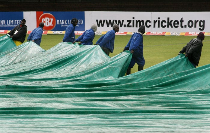 Zimbabwean cricket groundsman uncover the ground after the rain stopped play.(AFP PHOTO)