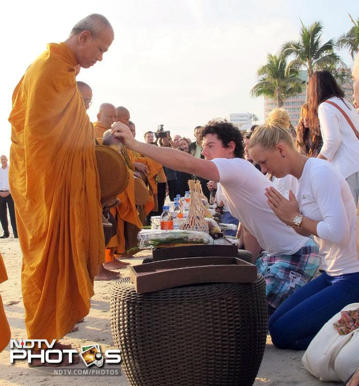 Caroline Wozniacki of Denmark (R) and men's world number three golfer Rory McIlroy during a religious ceremony at Hua Hin resort. (AFP PHOTO / BEC Tero)