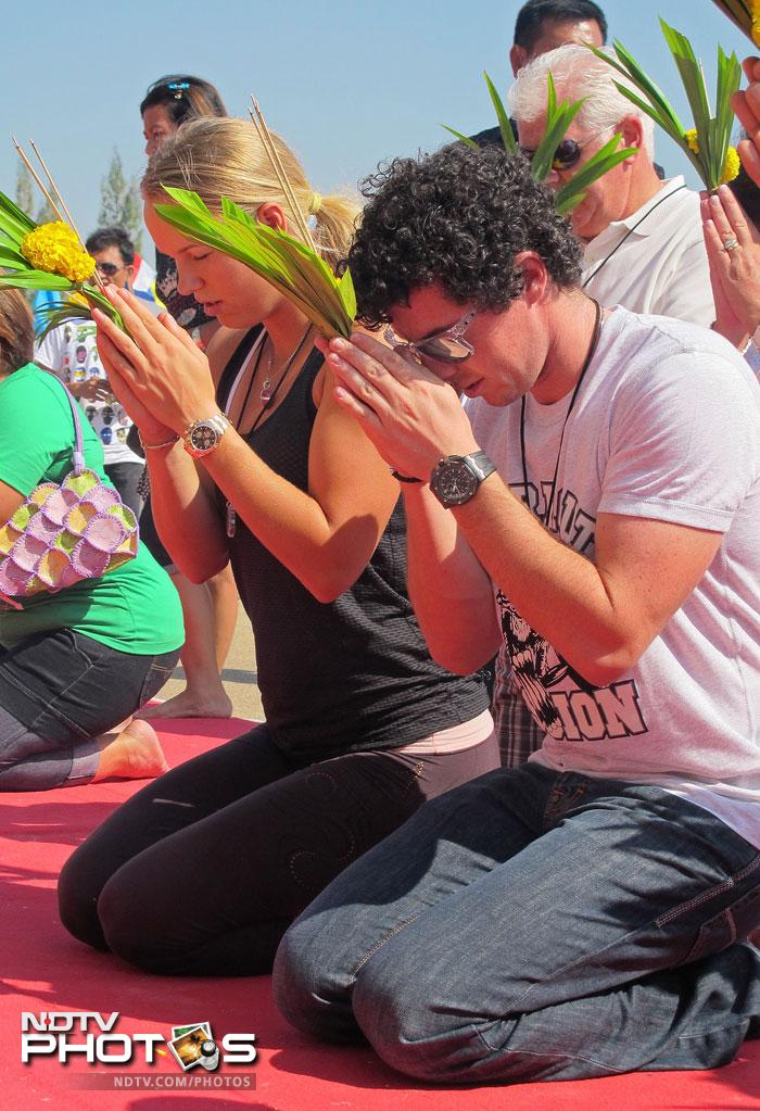 Wozniacki and McIlroy praying at the Buddhist temple in Thailand. (AFP PHOTO/HO/BEC Tero)