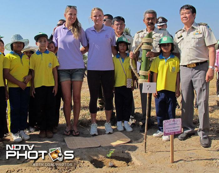 Caroline Wozniacki of Denmark (4L) and Victoria Azarenka of Belarus (3L) posing for a photo with Thai children during a tree planting project in honour of Thai King Bhumibol Adulyadej at Hua Hin resort. (AFP PHOTO/HO/BEC Tero)