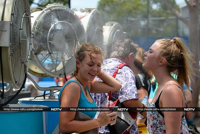 Two young fans let their hair down in front of the water fans.