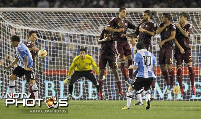 Lionel Messi, 10, takes a free kick against Venezuela during a friendly soccer match in Kolkata. (AP Photo)