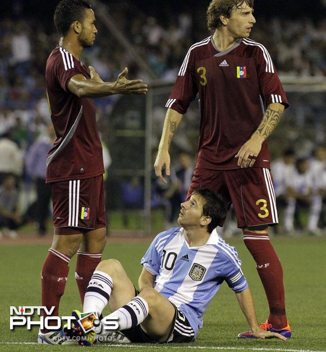 Lionel Messi, on ground, after he fell during a tackle by Venezuelan defenders Angel Flores and Fernando Amorebieta in Kolkata. (AP Photo)