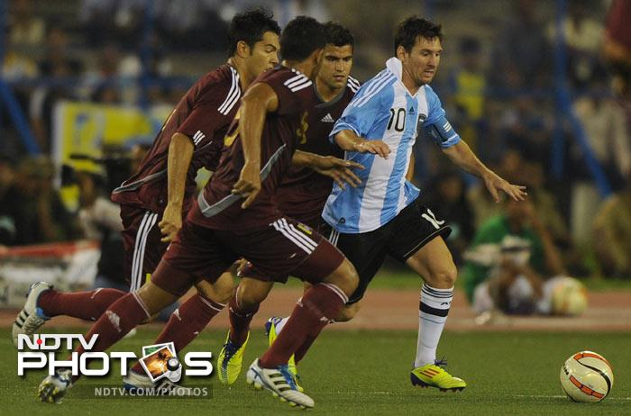 Lionel Messi tries to get past players from Venezuela during a football match in Kolkata. (AFP Photo)