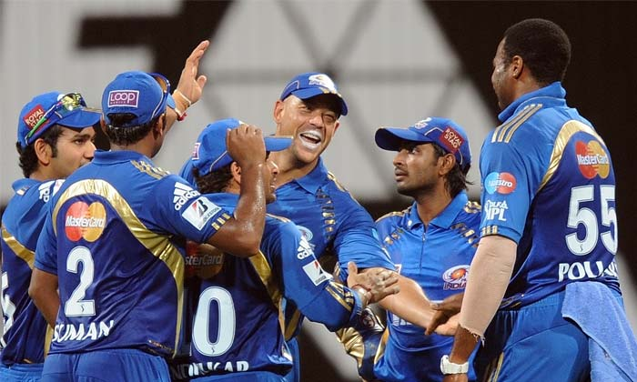 Mumbai Indians bowler Kieron Pollard (R) celebrates with Andrew Symonds (C) and other teammates after taking the wicket of Deccan Chargers batsman Sunny Sohal during the IPL Twenty20 cricket match at the Wankhede Cricket stadium in Mumbai. (AFP PHOTO)