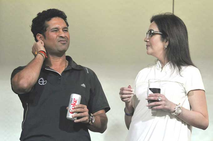 """Now Sachin need not go on a diet but he may just be drinking that for the taste. He is seen here with team owner Neeta Ambani although the expression on his face is best left not-understood. (Photo courtesy: <a href=""""http://www.mid-day.com//"""">Mid-day.com</a>)"""