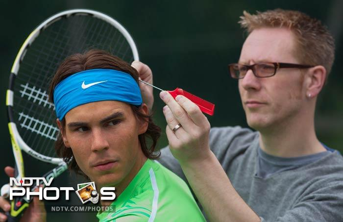 Roger Mackay of Madame Tussauds, poses for pictures as he puts the finishing touches to a new waxwork figure of Nadal at a photocall in Regents Park in central London. (AFP Photo)