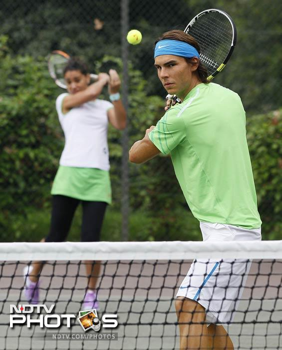 Tennis coach Emily Taylor plays doubles with a model of Rafael Nadal at a tennis centre in Regents Park in London. (AP Photo)