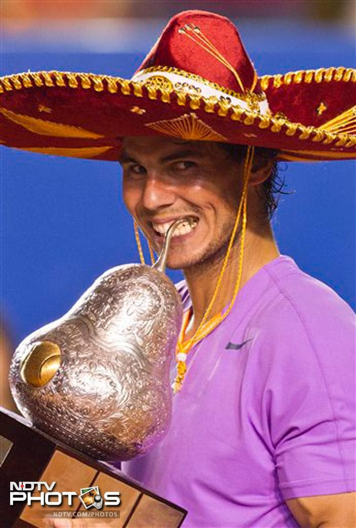 Nadal poses with the Mexican Open title in his customary way, biting the trophy while sporting a Mexican matador hat.