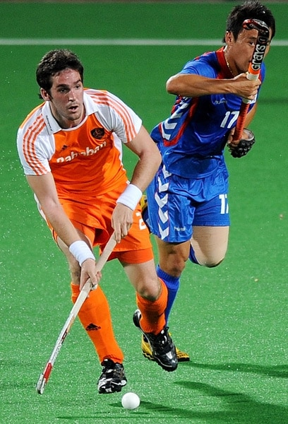 Netherlands hockey player Robert van der Horst (L) vies for the ball with South Korean hockey player Hong Eun Seong(R) during their World Cup 2010 match at the Major Dhyan Chand Stadium in New Delhi. (AFP Photo)
