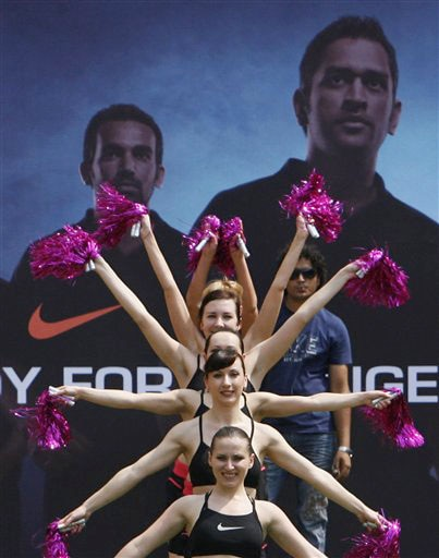 Cheerleaders perform before an event to showcase the new apparel for the Indian one-day international team in Mumbai on Wednesday. In the backdrop are photographs of Mahendra Singh Dhoni and Zaheer Khan. (AP Photo)