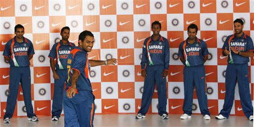 MS Dhoni displays the new apparel for the Indian one-day international team, as teammates, background from left, Zaheer Khan, Dinesh Karthik, Pragyan Ojha, Rohit Sharma and Yuvraj Singh look on, in Mumbai on Wednesday. (AP Photo)