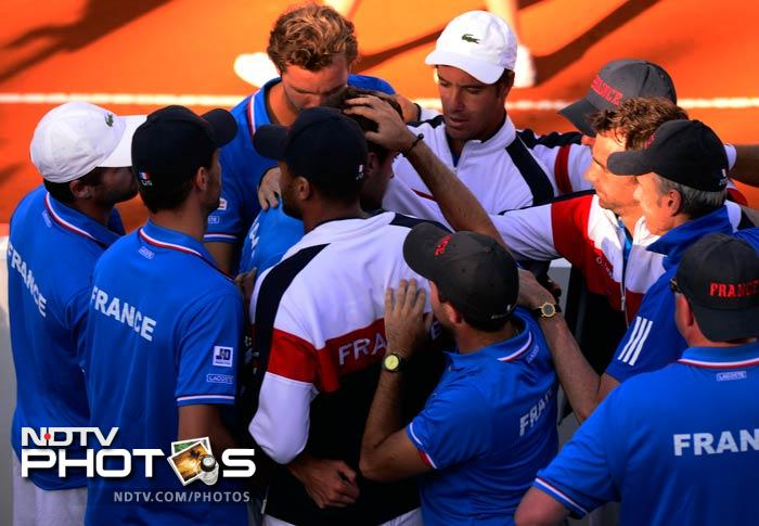 France players confort teammate Gilles Simon after he lost 6-4, 5-7, 6-4, 6-4 against Carlos Berlocq of Argentina in Davis Cup World Group quarterfinal singles match.