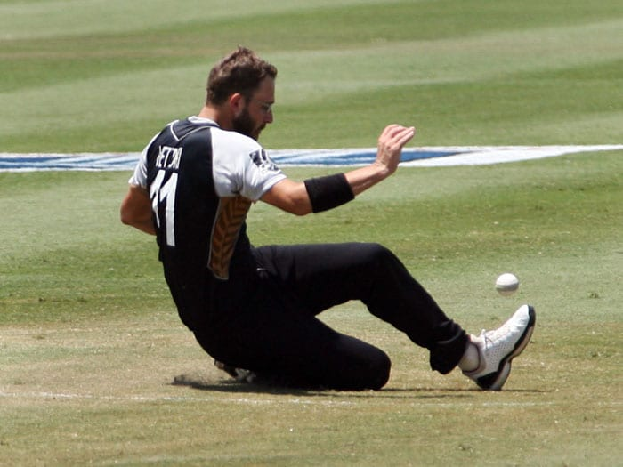 New Zealand bowler Andy McKay attempts to stop a ball with his feet.Mc Kay finished with figures of 11/0 in his 2 overs. (AP PHOTO)